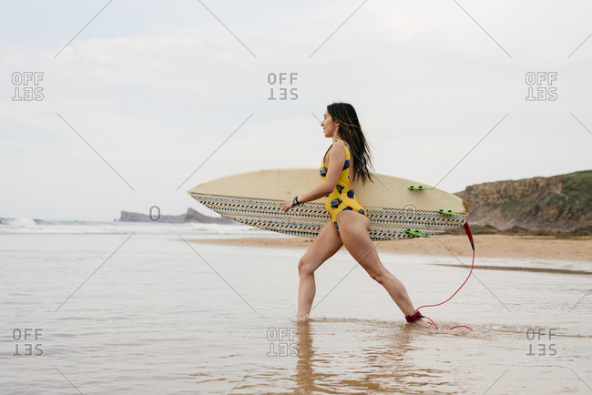 Blonde girl walking on the seashore with a surfboard
