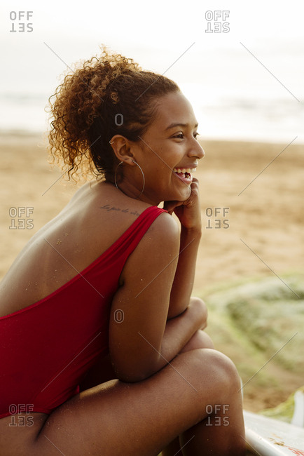Pretty black girl sitting on the rocks with a surfboard at sunset