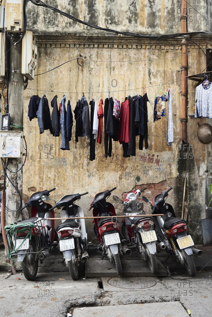 Hanoi, Vietnam - February 28, 2018: Motorbikes and clean clothes hanging on the street