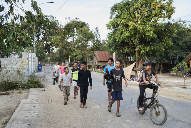 Central Highlands, Vietnam - January 9, 2018: Local Vietnamese group of friends carrying a chicken in small village
