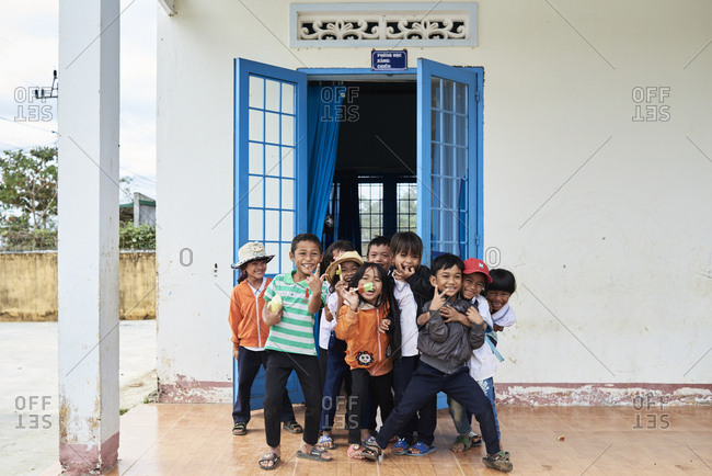 Central Highlands, Vietnam - January 10, 2018: Group of primary school students outside classroom super happy making fun