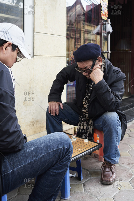 Hanoi, Vietnam - February 28, 2018: Two males playing Vietnamese chess on the street