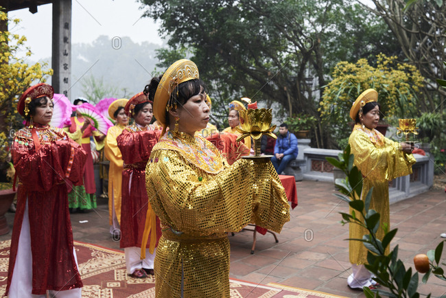 Hanoi, Vietnam - February 24, 2018: Vietnamese women leading a ceremony wearing traditional costume during Tet celebration inside Ngoc Son temple