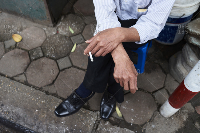 Overhead of male hands holding a cigarette with crossed legs, Hanoi, Vietnam