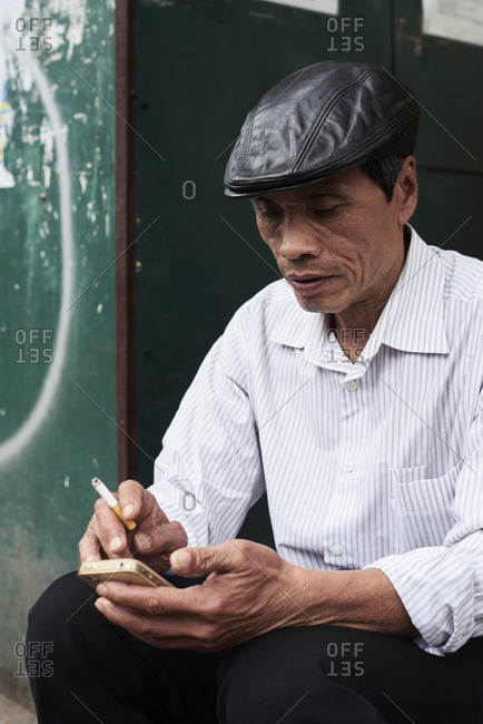 Hanoi, Vietnam - February 28, 2018: Stylish senior Vietnamese man typing on smartphone with cigarette and beret