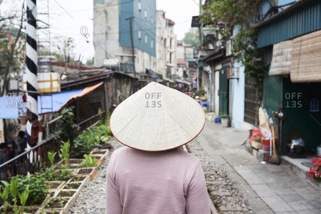 Faceless Vietnamese woman walking on the train street wearing traditional hat, Hanoi, Vietnam
