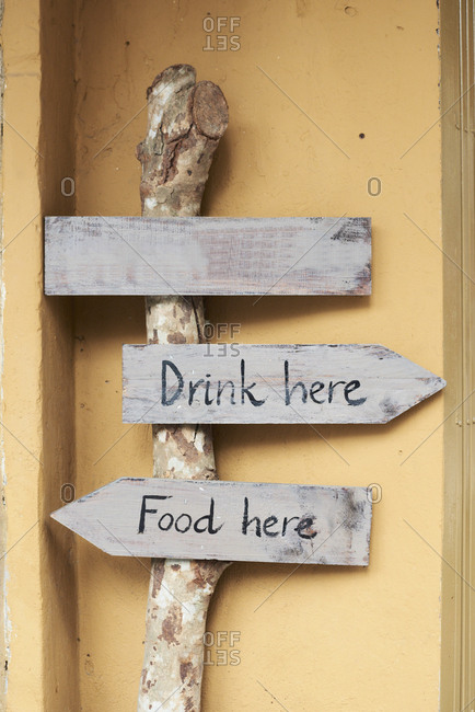 Hand-written wood sign boards with messages of drink and food here pointing in opposite directions
