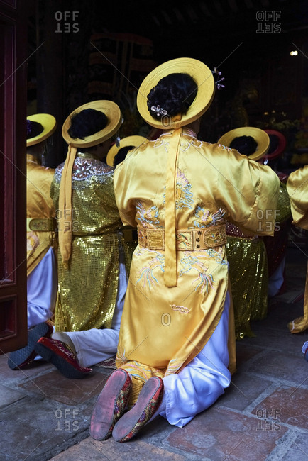 Back view of Vietnamese women in a ceremony wearing traditional yellow costume during Tet celebration, Hanoi, Vietnam