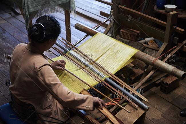 Woman working making silk in a wooden house fabric, Central Highlands, Vietnam