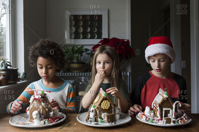 Siblings sitting at the kitchen table with their gingerbread houses