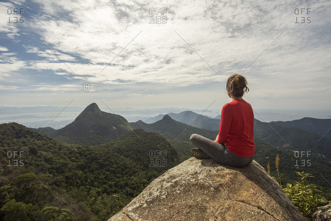 Rear view of single woman sitting on rock in scenery with mountains, Tijuca Forest National Park, Rio de Janeiro, Brazil