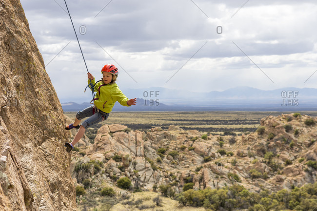 A girl rock being lowered down a cliff face after rock climbing on the Trad Wall, Isle of You, Cochise Stronghold, Tombstone, Arizona, USA