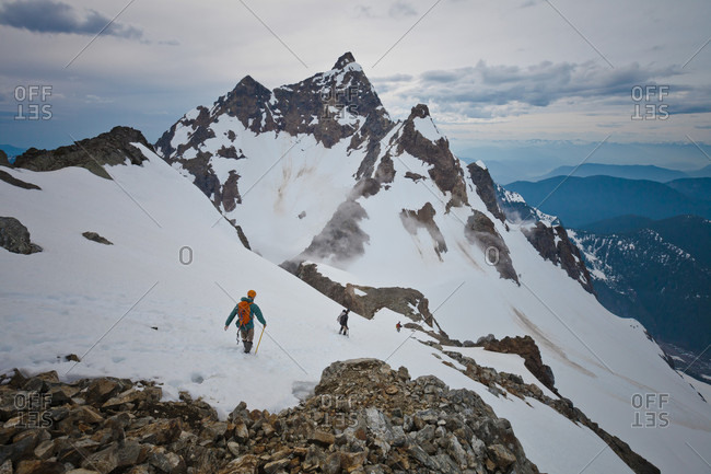 Distant view of three adventurous mountain climbers climbing Foley Peak, North Cascade Mountain Range, Chilliwack, British Columbia, Canada