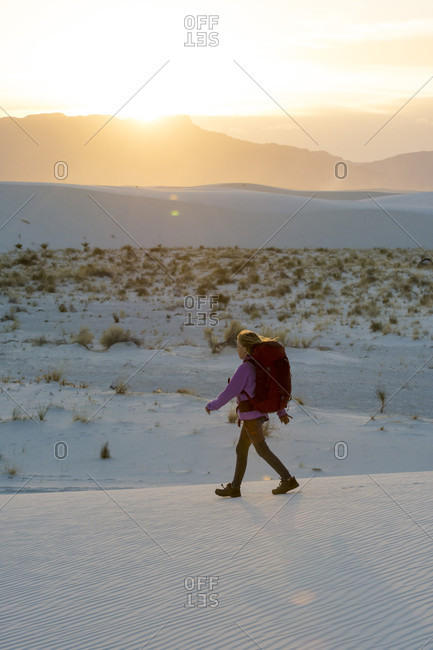 Side view of girl hiking at sunset in White Sands National Monument, Alamogordo, New Mexico, USA