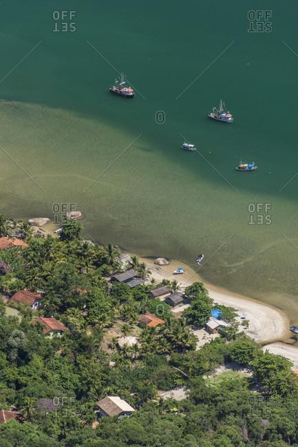 View of fishing village and fishing boats in sea from Mamangua Peak, Saco do Mamangua, Paraty, Costa Verde, Brazil