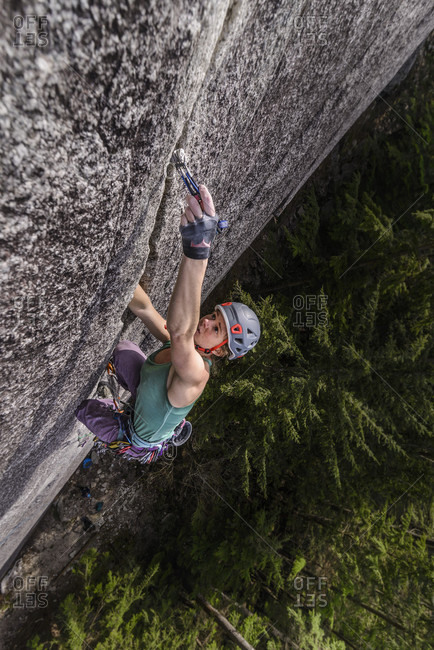 View from above of single adventurous woman rock climbing up cliff, Squamish, British Columbia, Canada
