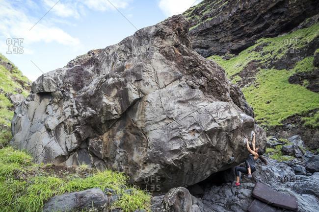 Distant view of adventurous woman climbing boulder, Maui, Hawaii Islands, USA