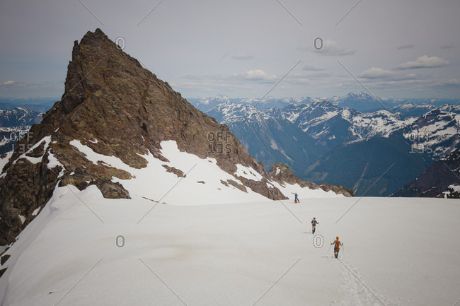 Distant view of three climbers approaching Foley Peak in the North Cascade Mountain Range, Chilliwack, British Columbia, Canada