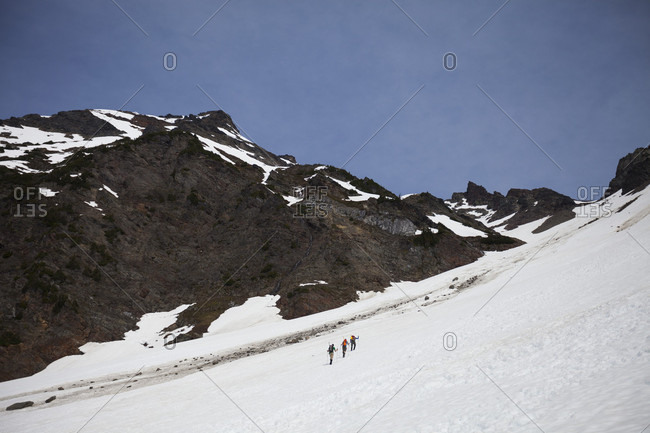 Distant view shot of mountain climbers climbing Foley Peak, North Cascade Mountain Range, Chilliwack, British Columbia, Canada