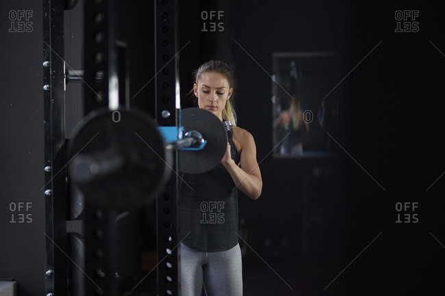 Young blonde woman in sportswear in gym preparing to weightlift with barbell