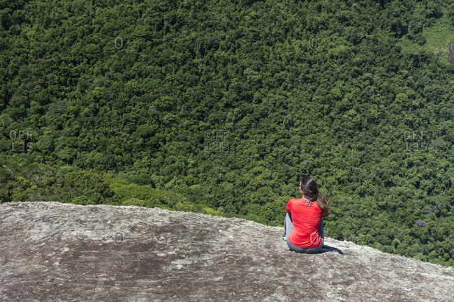 Rear view of single woman sitting on rocky mountain overlooking forest, Saco do Mamangua, Paraty, Costa Verde, Brazil
