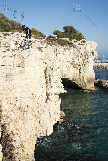 Distant view shot of adventurous mountain biker on coastal cliffs