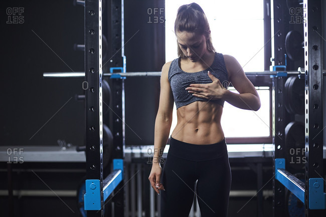 Three quarter length shot of woman with muscular abdomen in gym