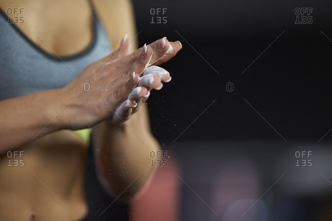 Close up of woman in sportswear applying sports chalk on hands