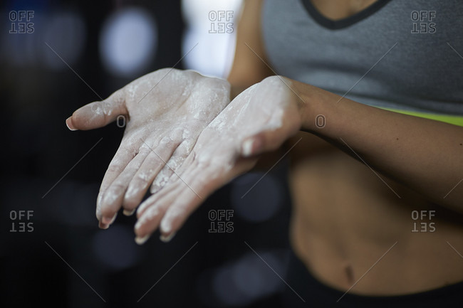 Close up of woman in sportswear with sports chalk on hands