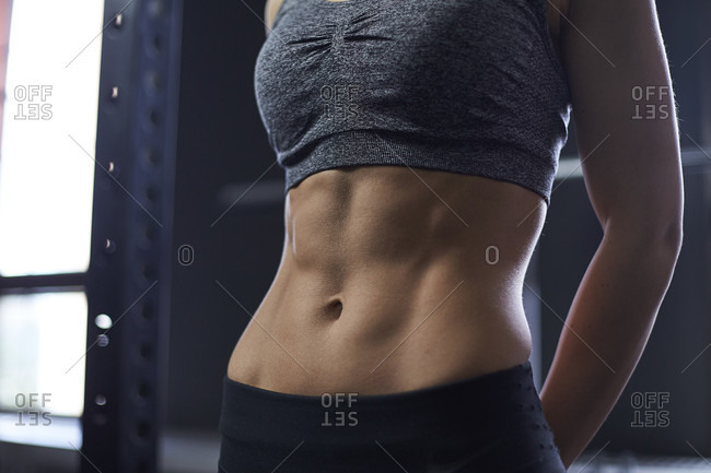 Mid section shot of woman with muscular abdomen in gym