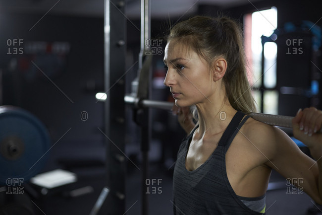 Full length shot of woman exercising in gym with exercise machine
