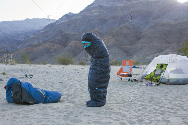 Boy and teenage girl playing with sleeping bags, Death Valley National Park, California, USA