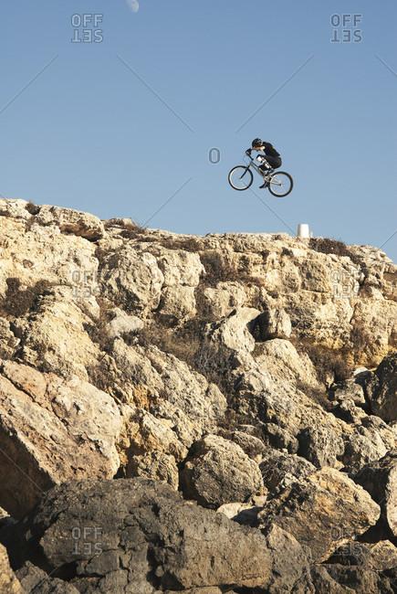 Side view of adventurous mountain biker in mid-air over rocky terrain under clear sky