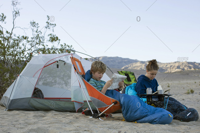 Boy and teenage girl camping in desert with boy looking at map, Death Valley National Park, California, USA
