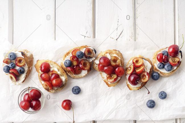 Bruschetta with cherry, blueberry, honey sauce and cream cheese