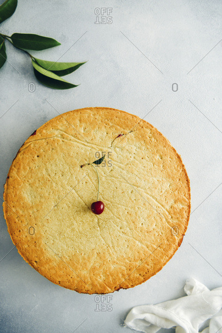 Cherry pie topped with a cherry on grey background photographed from top view Green leaves and white linen accompany
