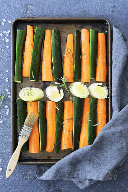 Raw strips of carrot and zucchini with sliced leek on a baking tray