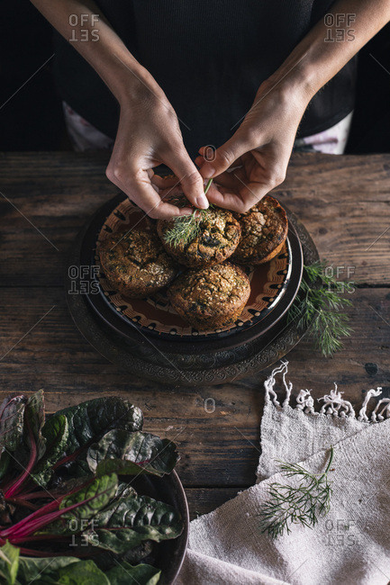 Persons hands with corn muffins bread with leaf of chard