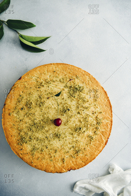 Cherry pie topped with a cherry and ground pistachio on grey background photographed from top view Green leaves and white linen accompany