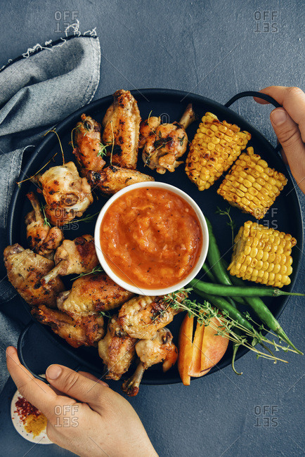 A woman serving a chicken wings platter with grilled corn on the cob, green peppers, fresh thyme, peach slices and a sugar free bbq sauce in the middle photographed on a dark background from top view