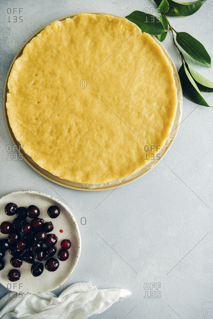 Pie dough, pitted cherries and green leaves on grey background photographed from top view