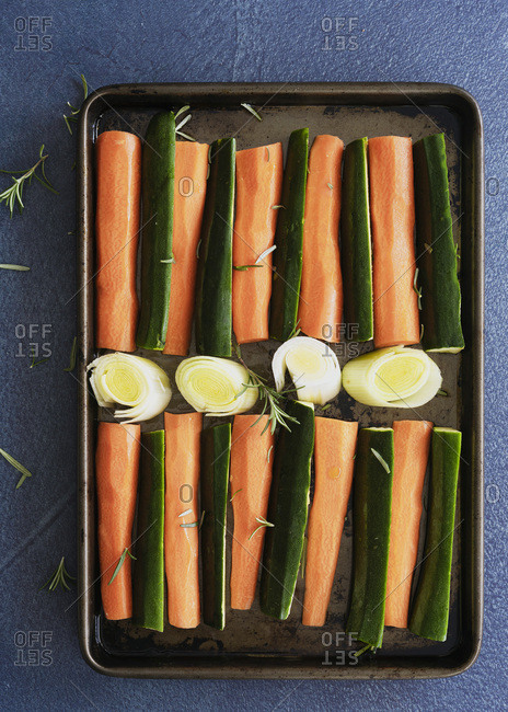 Raw carrot, zucchini and leek on a baking tray ready for roasting