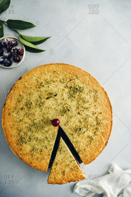 A cherry pie topped with a single cherry and ground pistachio with one slice photographed from top view Green leaves, pitted cherries on a small plate and white linen accompany