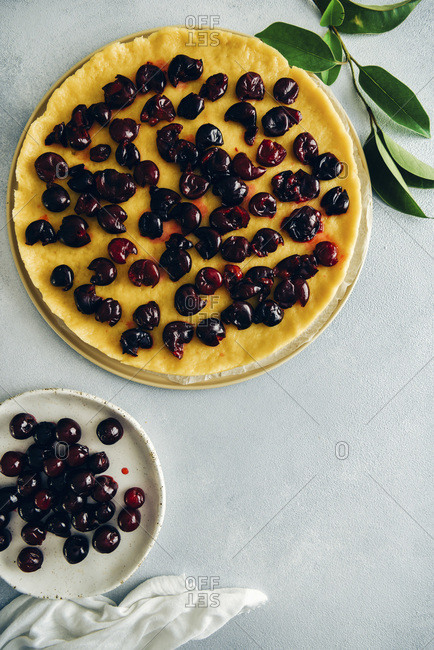 Pie dough topped with cherries, pitted cherries on a white plate and green leaves on grey background photographed from top view