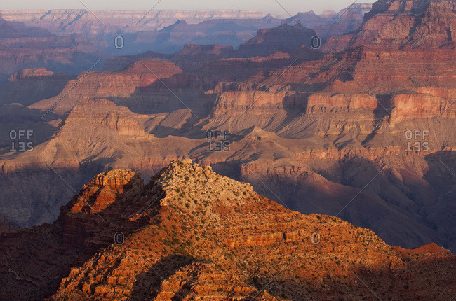 Looking west over the Grand Canyon's North Rim as dawn sweeps shadows across the landscape.