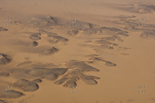 An aerial view of a rock and sand dune pattern in desert sand.