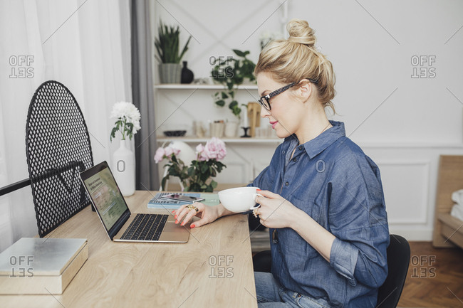 Beautiful blonde Caucasian freelance businesswoman sitting at her home office and working on her laptop