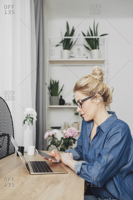 Beautiful blonde Caucasian freelance businesswoman sitting at her home office and typing on cell phone