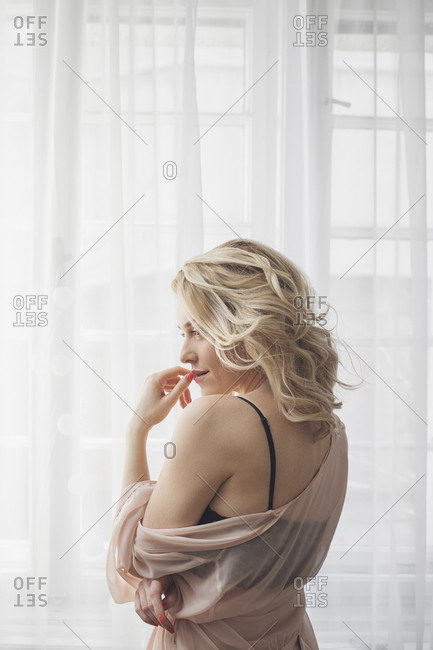 Back view of beautiful sensual Caucasian blonde woman standing by the window in lingerie