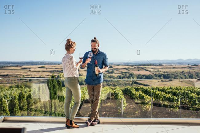 Couple enjoying drinking wine at vineyard